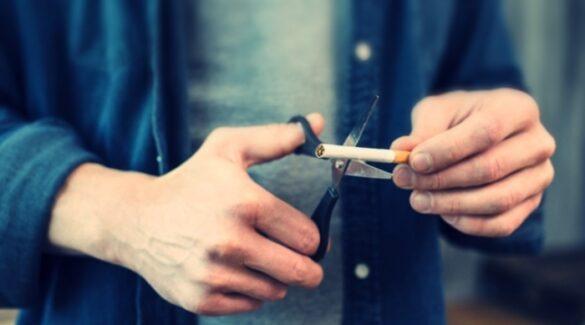 Persona cortando un cigarrillo con una tijera
