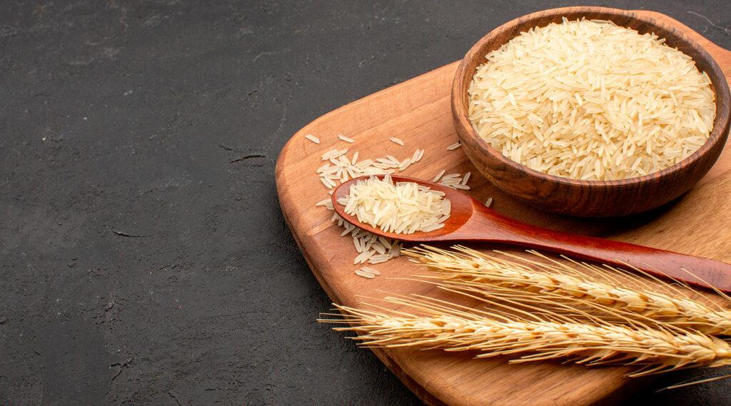 Tabla de madera con un plato de arroz crudo y unas espigas.