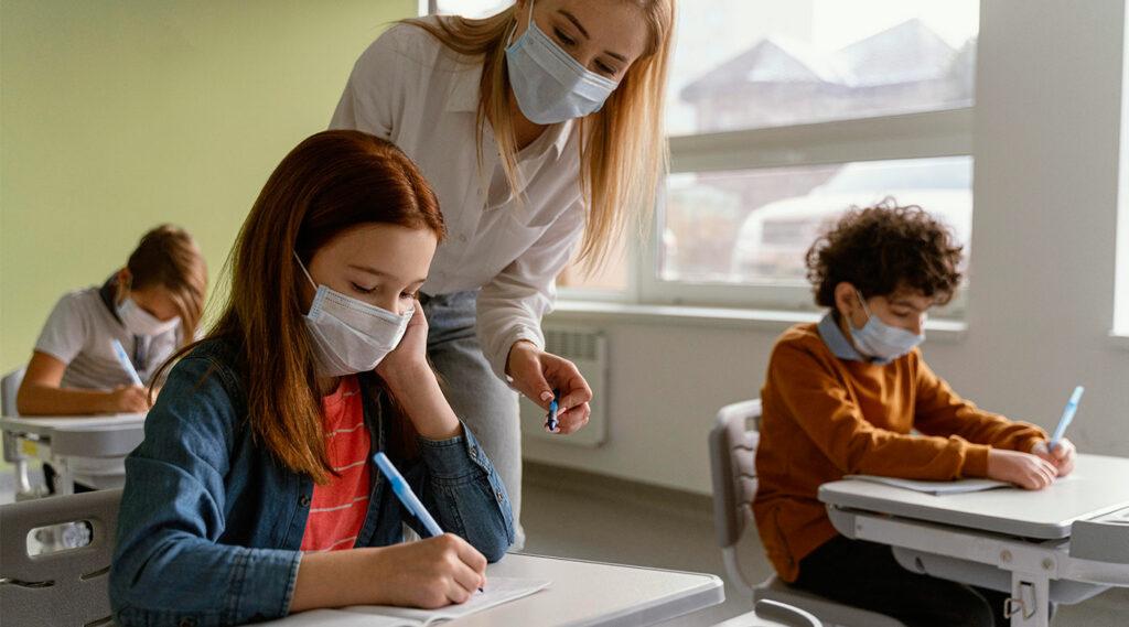Niños con máscaras médicas que estudian en la escuela con el maestro