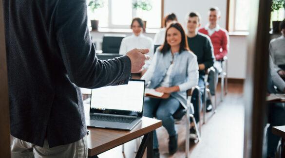 Estudiantes sonrientes en aula, oyendo al profesor.