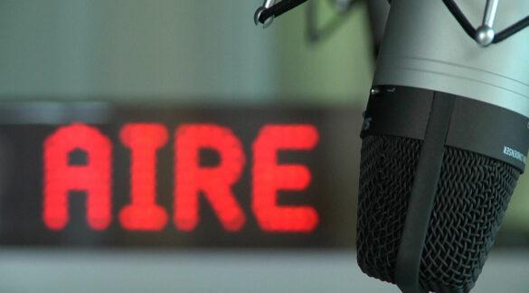 """estudio de radio con micrófono omnidireccional y cartel de """"Aire"""""""