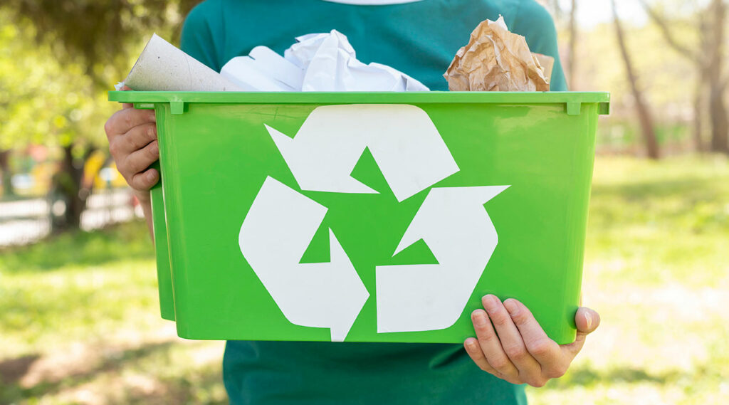 Hombre sosteniendo un canasto con residuos para reciclar.