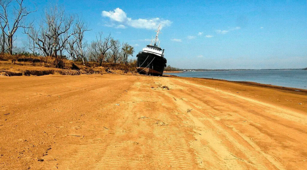 Un barco encallado en la orilla y el río bajo