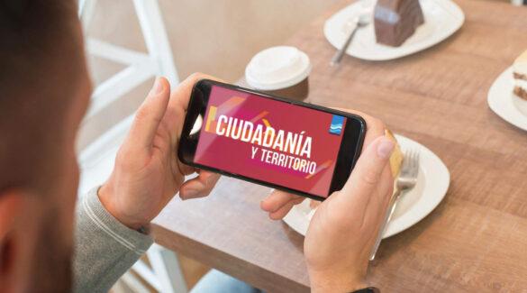 Manos sosteniendo un smartphone con el logo del programa Ciudadanía y Territorio