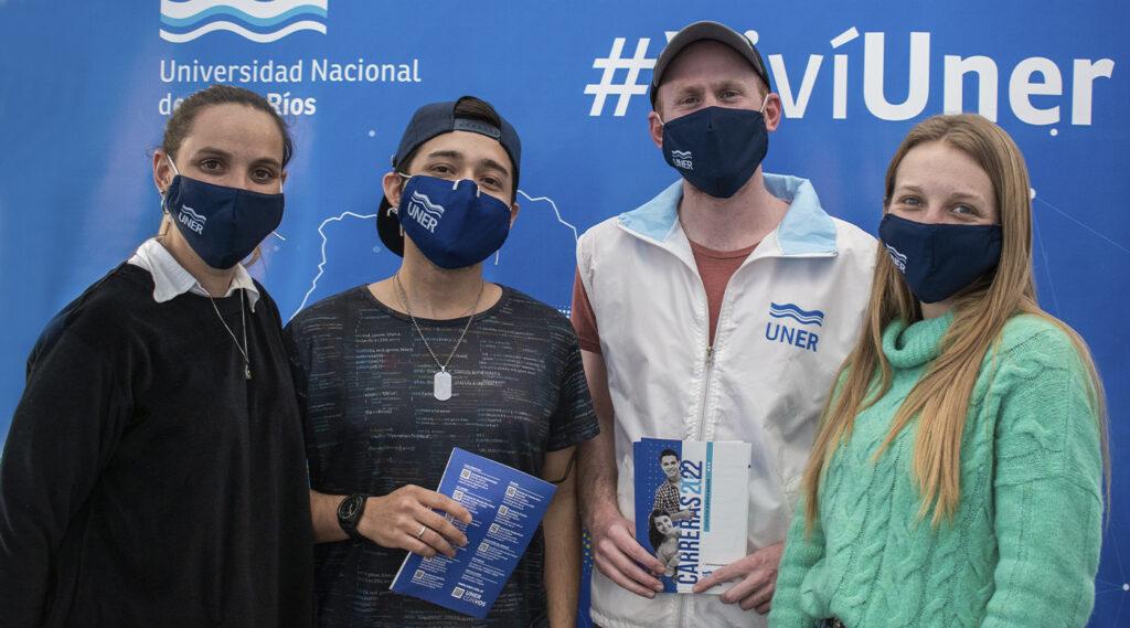 Cuatro becarios de difusión posan frente al cartel de UNER en el stand de la feria El Becario te Muestra 2021.