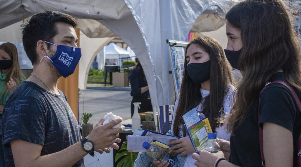 Joven dialoga con estudiantes frente al stand de UNER.