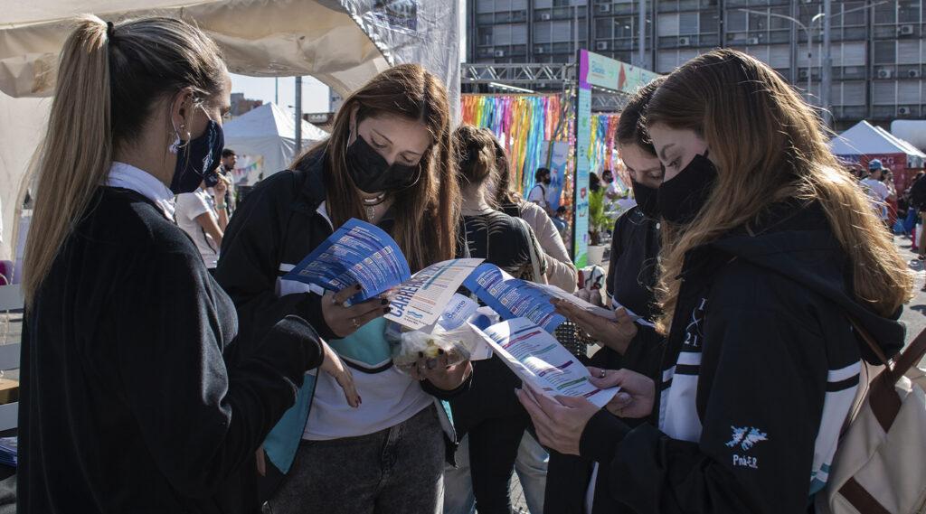 Estudiantes mujeres observan los folletos con las carreras de la UNER.