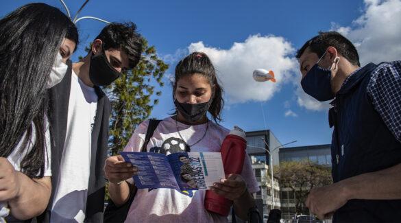 Estudiantes viendo folleto de difusión de carreras de la UNER