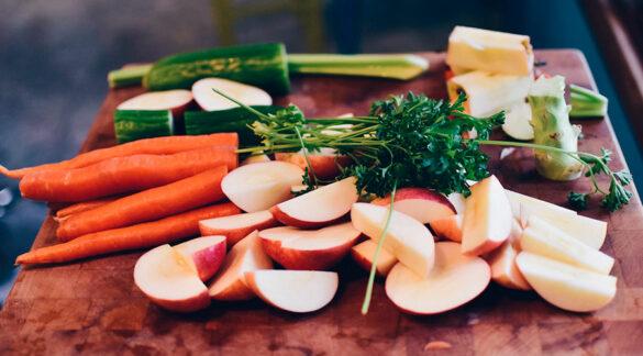 Mesa con trozos de manzana, zanahoria, perejil y otras hortalizas.