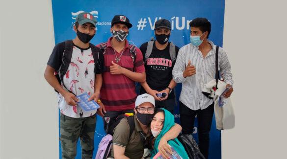 Estudiantes de la escuela secundaria de la UNER posan frente a un cartel de la UNER en la feria El Becario te Muestra.