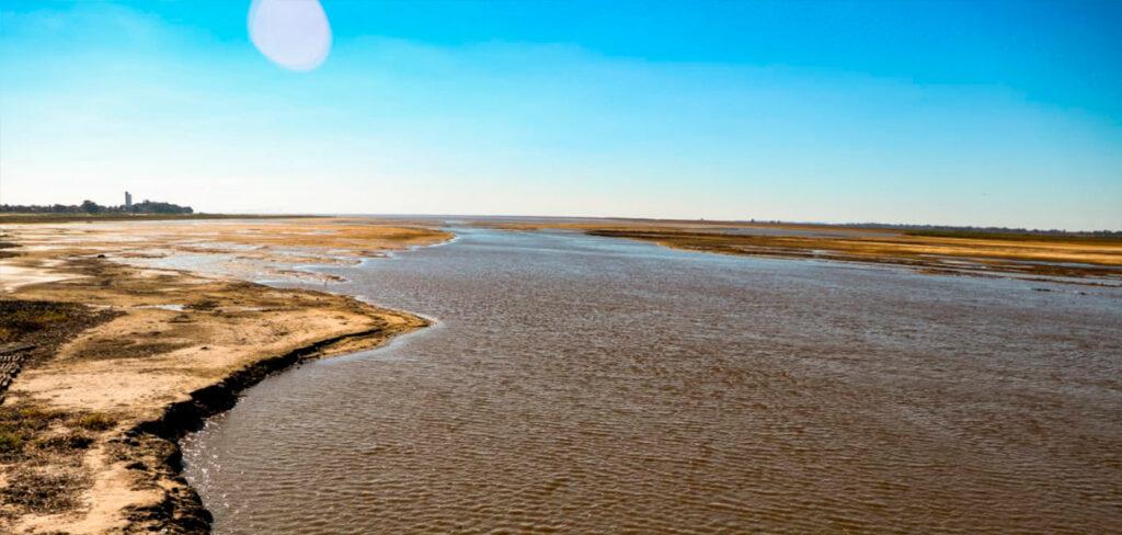 Río paraná con poca agua, de lejos se observa una ciudad.