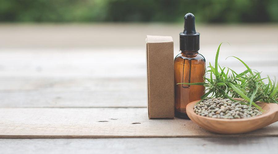 Hojas de cannabis junto a un gotero con aceite medicinal de cannabis