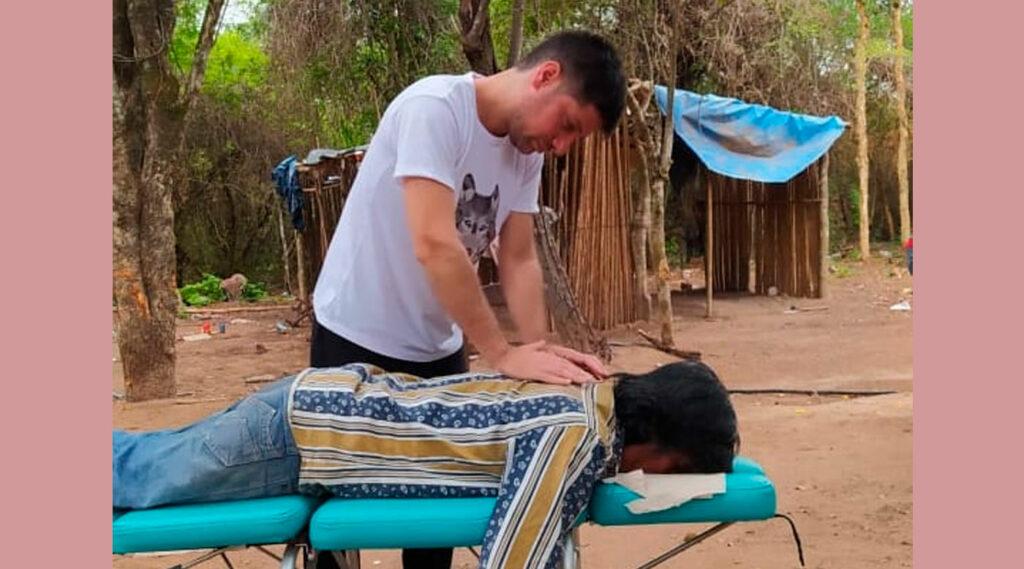 Un estudiante de Kinesiología atiende un paciente sobre una camilla.